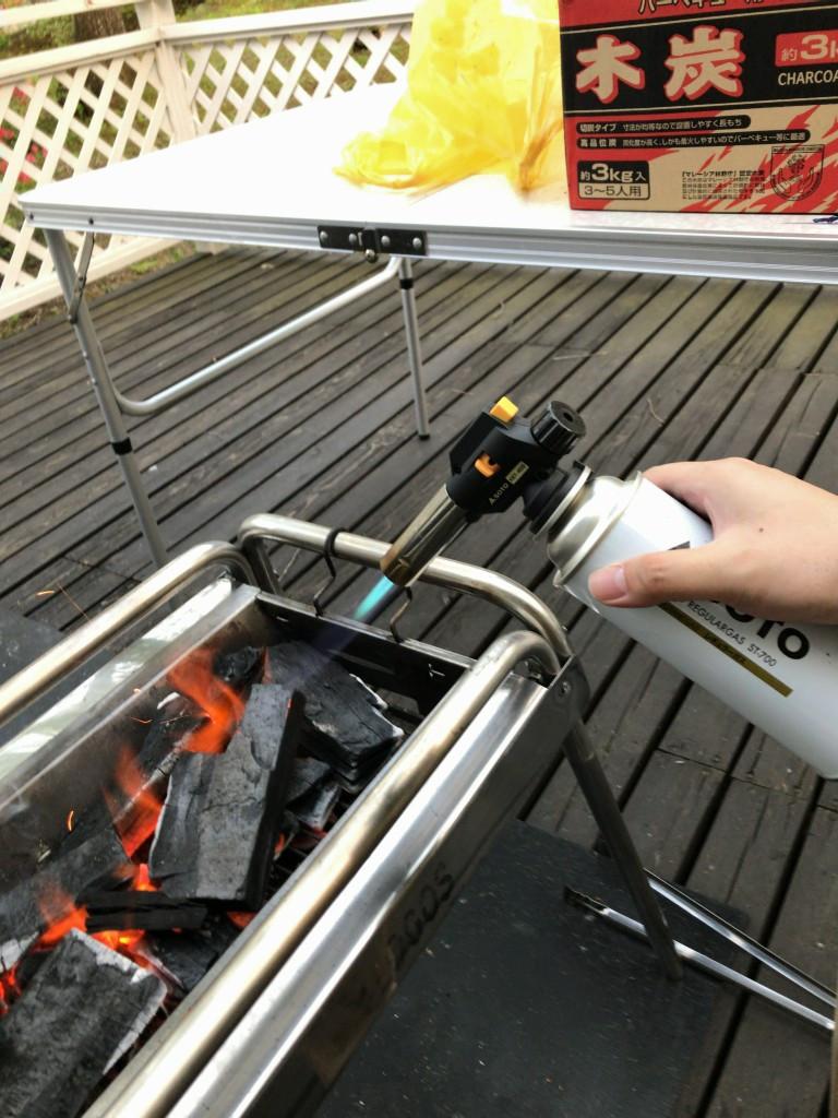 ウッドデッキのテラスでバーベキュー用に久々の火起こし中。グリル機材一式もレンタル出来て、持ち込み荷物も減らせました(このバーナーは私物(後述))。